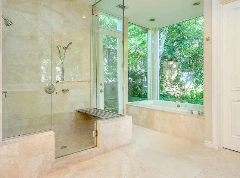 bathroom with cream marble floor, shower, and tub surround