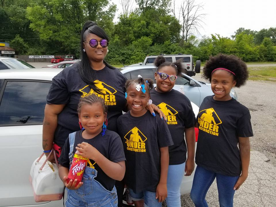 love local adult volunteer standing with four young girls