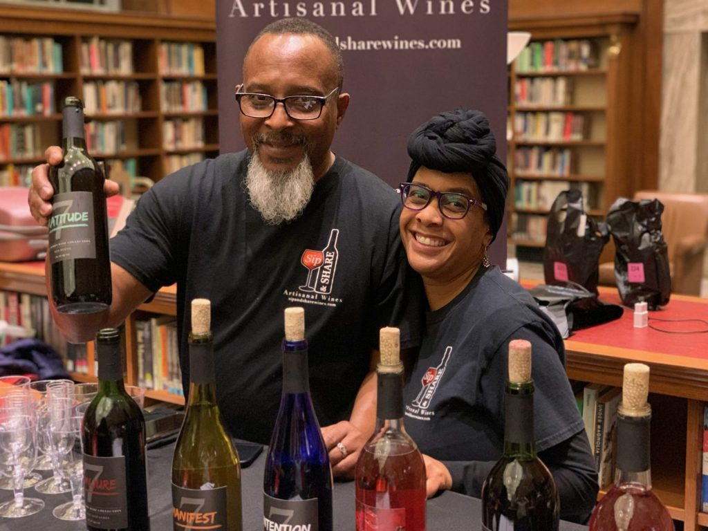 love local man and woman behind wine sampling table