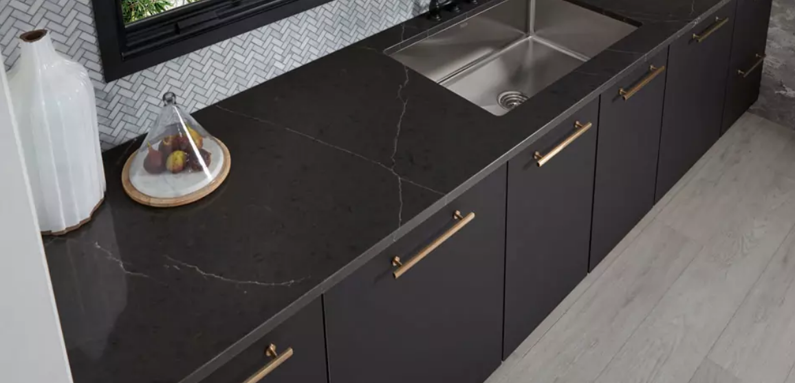 ariel view of dark countertop with light veining and gold cabinet fixtures